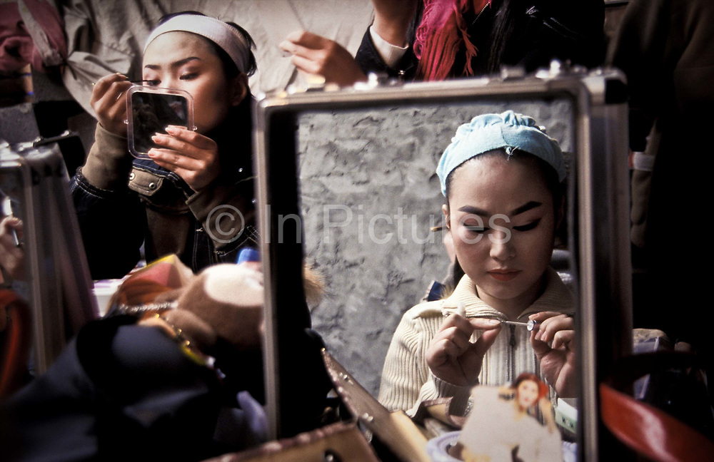 Zhang Lin, 23 leading Yue opera performer from the Xiao Bai Hua Shaoxing Opera Troupe in final stages of putting on her make-up before a performance in a rural village close to Shaoxing City, Zhe Jiang province, China.                                She is one of the leading ights of Yue opera which as a form was born as late as the 1930's and she's been part of this troupe since she was 14. Today Yue opera like all traditional art forms faces stiff competition from television and all sorts of other entertainment and  as the troupe  no longer receive significant state funding, they must perform at least 150 times a year travelling far and wide across the country
