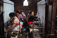 Women weave carpets in a small factory in Kathmandu, Nepal. The women are paid based on the amount of carpet they weave and earn from $4 to $10 a day.
