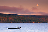Full moon setting over fog Tomales Bay and lone dory boat at sunrise near Point Reyes Marin California Full moon setting and fog at sunrise over lone boat in calm water, Tomales Bay, Marin County, California