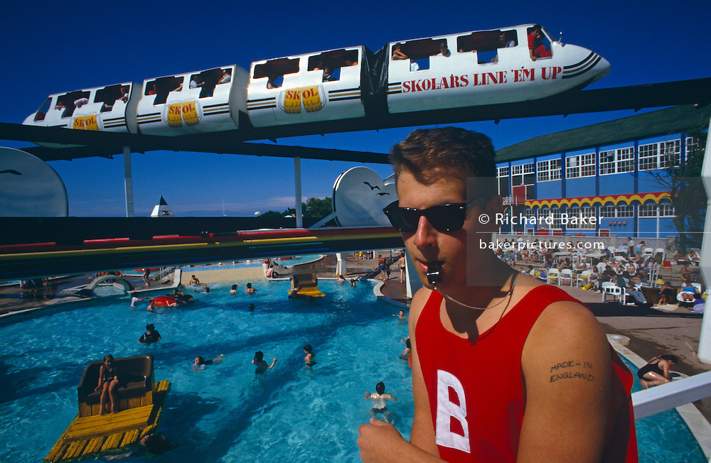 At the famous Butlins holiday camp in the Somerset town of Minehead, a poolside lifeguard overlooks the main  pool from an overhead bridge. Behind him a monorail transports holidaymakers around the resort. Wearing the large letter B for Butlins on his red vest, the young lad sucks on his whistle held between his lips and prominently, the words 'Made in England' have been tattooed on his left shoulder - as if a statement for his patriotic ideals but also for those of Butlins - an institution for the British working classes who after the war had the opportunity to spend their summers at special resorts in seaside towns that provided entertainment and fun. Butlins and other camp businesses went into decline when the masses preferred Spanish vacations but have since been revived as travel costs have again soared and holidays at home are once again popular.