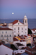 View from Portas do Sol belvedere to Alfama district and a magnificent full moonrise over the Tagus river. In highlights the Santo Estêvão church.This is part of the way of Lisbon's nº28 yellow tram, through the central, most historic region of the city.