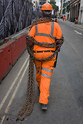 As a metaphor to the toil and struggle of life and work, a construction site contractor carries heavy chains along the street in front of a hoarding featuring many faces, on the corner of Limeburner Lane and Ludgate Hill, EC4. The construction and development company Skanska is responsible for its design, maintaining a clean and tidy site, separating the dangers of the site and Londoners at street level. The links of the chain drag behind him, as he lumbers on before dropping them to the ground around the corner.