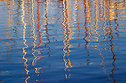 Reflections of sail boat masts in the sea water in the harbour. Barcelona, Catalonia, Spain.