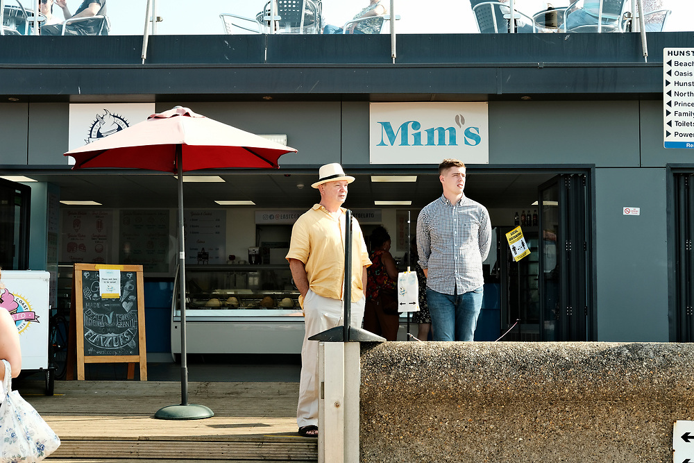 In the bright summer sun, two men stand outside the East Cost Geleto Parlour on the seafront in Hunstanton.<br /> Taken on the last hot day of the Summer in Hunstanton Norfolk, the first summer in the UK during the COVID-19 pandemic.<br /> <br /> Photo by Jonathan J Fussell, COPYRIGHT 2020
