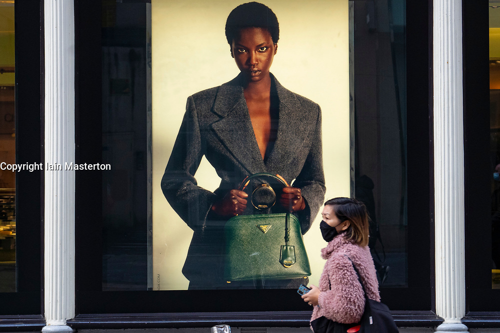 Glasgow, Scotland, UK. 26 October 2020. View of Glasgow city centre on weekday during circuit breaker lockdown with bars and restaurants closed. Pictured;  Woman in facemask walks past window display for Prada in Frasers department store. Iain Masterton/Alamy Live News