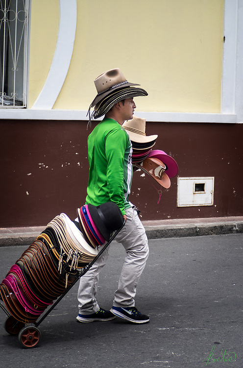 A man pedaling hats, with multiple hats on his head, in his hand and on a cart he is pulling.