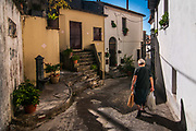 An old woman walks in the streets of the village of Aieta, Italy. Aieta (also written in Ajeta form) is an Italian municipality of 814 inhabitants in the province of Cosenza in Calabria. Municipal territory is an integral part of the Pollino National Park.