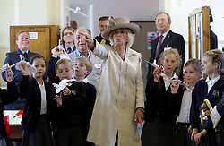 The Duchess of Cornwall throws a paper plane with school children from Halton Community Combined School during a visit to RAF Halton in Aylesbury.