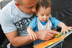 Father and son reading book.