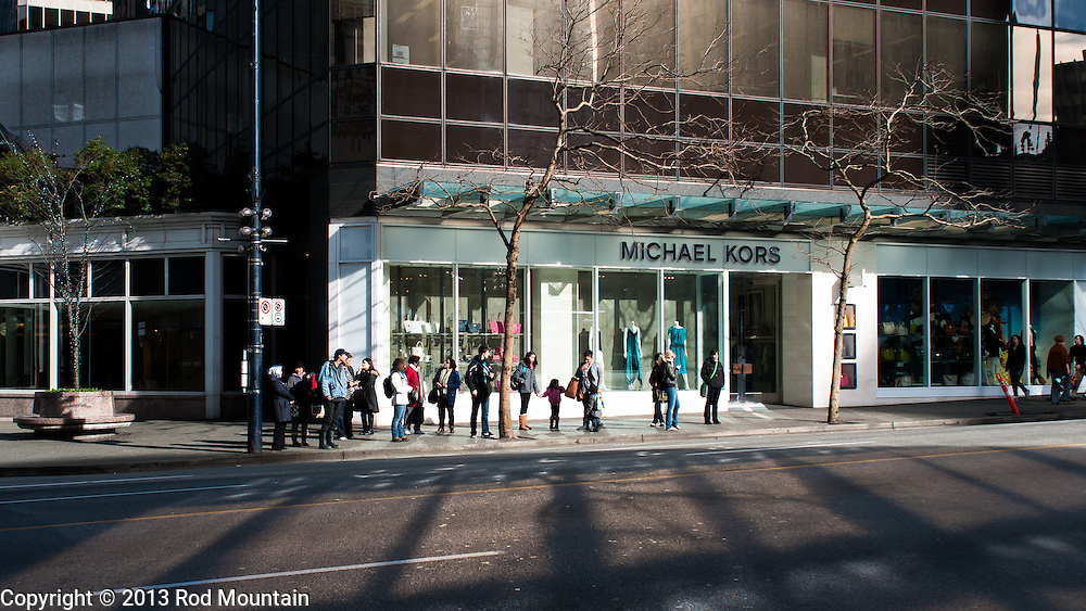 Transit riders waiting as the late afternoon sun reflects off the Michael Kors store in Vancouver, BC.
