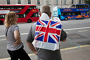 Tourist with a Union Jack flag carrier bag from one of the nearby souvenir shops in Westminster, London, United Kingdom.