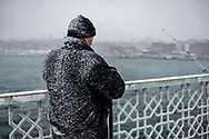 A man fishes on a snowy winter day from the Galata Bridge in Istanbul, Turkey. (January 8, 2013)