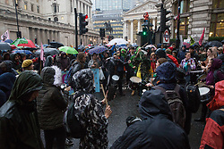 London, UK. 14 October, 2019. Climate activists from Extinction Rebellion endure an early evening downpour as they continue to occupy the busy junction in front of the Bank of England which they first occupied at around 7am on the eighth day of International Rebellion protests.