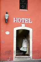 Hotel employee takes a quiet break, hotel doorway, San Miguel de Allende Mexico