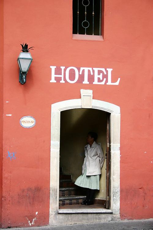Hotel employee takes a quiet break, hotel doorway, San Miguel de Allende Mexico