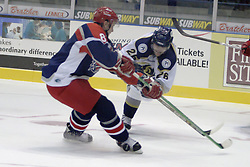 11 November 2006: B.J. Gaustad is cross checked by Chris Mann while trying to get past to the puck.&#xD;The Elmira Jackals met the Bloomington PrairieThunder at the U.S. Cellular Coliseum in Bloomington Illinois.<br />