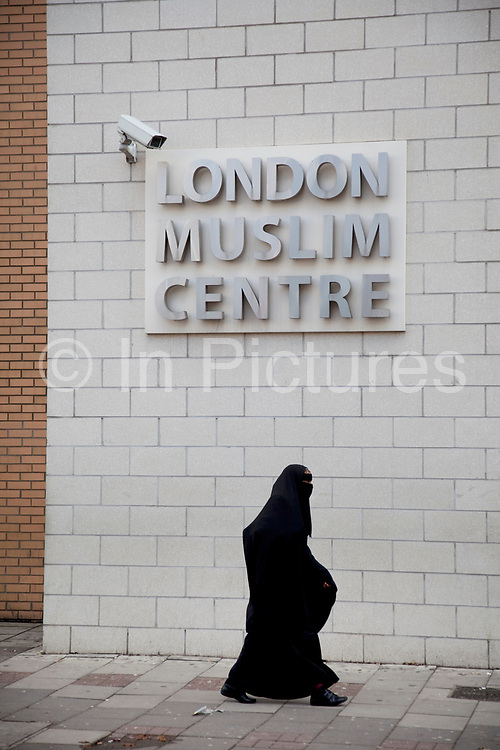 Woman wearing a burkha passes the London Muslim Centre under a CCTV surveillance camera on Whitechapel High Street in East London. This area in the Tower Hamlets is predominantly Muslim with just over 50% from Bangladeshi descent. This is known as a very poor area of London's East End.