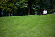 Man eating his lunch on the grass in a small park at the base of Canary Wharf, in East London's financial district. This is where office workers come to relax in some quiet away from the offices.