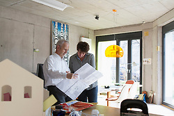 Two Architects discussing about blueprints in the office, Freiburg im Breisgau, Baden-Wuerttemberg, Germany