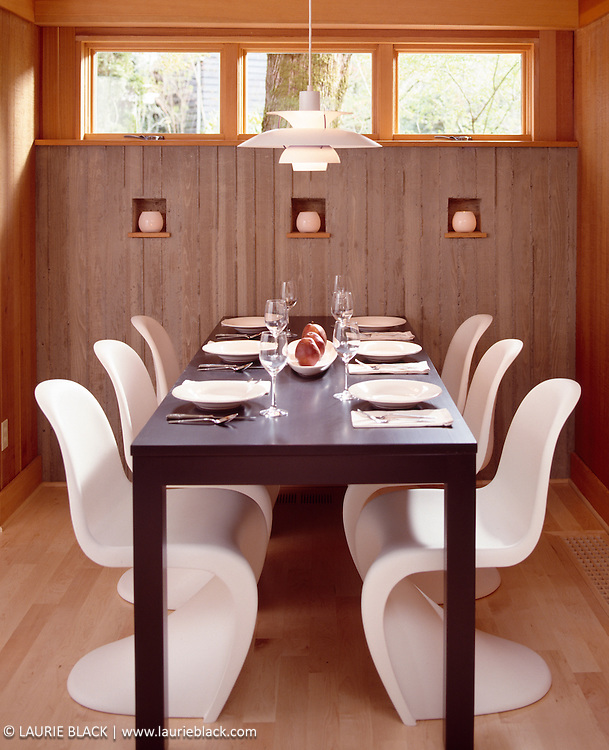 Contemporary dining table with white curved chairs.
