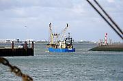 Nederland, Breskens, 5-9-2019 In de haven van deze kustplaats in Zeeuws Vlaanderen vaart juist een schip, vissersschip, kotter, uit richting open water, noordzee .Foto: Flip Franssen