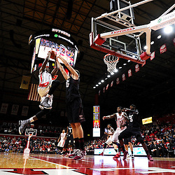 Kadeem Jack #11 of the Rutgers Scarlet Knights jumps to the basket against Jimmy McDonnell #15 of the Temple Owls during the first half of Rutgers men's basketball vs Temple Owls in American Athletic Conference play on Jan. 1, 2014 at Rutgers Louis Brown Athletic Center in Piscataway, New Jersey.