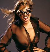 Stunning woman wearing sheer black blouse and goggles, breasts exposed, hair blowing, looking at camera and standing in front of a dark gray background.