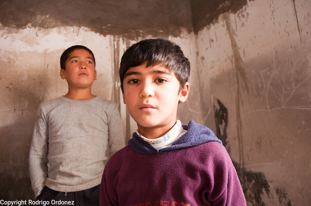 Two boys pose for a photograph during a distribution of food donated by the World Food Programme (WFP) in the neighborhood of Kizil Kishtak in Osh, Kyrgyzstan.