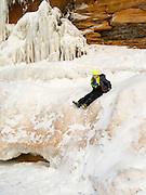 A boy slides off of an ice formation at the Apostle Island Ice Caves, Makwike Bay, near Bayfield, Wisconsin, on a cold February day.