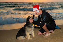 surfer wearing a Santa hat enjoying the company of a dog at sunrise