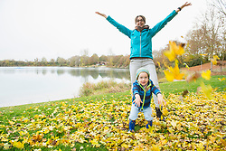 Mother and son throwing autumn leaves in air in front of lake