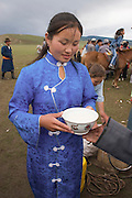 young girl serving a drink at the traditional horse back races at Nadaam, Mongolia