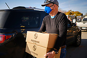 06 NOVEMBER 2020 - DES MOINES, IOWA: ORVAL BYRD, a volunteer with the Food Bank of Iowa, brings food boxes to a client's car during a drive through emergency food distribution at the Iowa State Fairgrounds Friday. A spokesperson for the Food Bank of Iowa said they had enough food for 1,500 families. Each family got frozen chicken legs, frozen liquid eggs, and fresh produce. There will be another emergency food distribution at the Fairgrounds on November 30. Food insecurity in the Des Moines area has skyrocketed since the start of the Coronavirus pandemic. Although unemployment rates in Iowa have fallen since a peak in June, many families that fell behind on rent are now facing eviction. The food bank spokesperson said use of the Food Bank's emergency pantries and distribution points is still increasing.     PHOTO BY JACK KURTZ