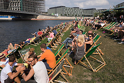 Busy outdoor cafe and bar beside Spree River in Berlin Germany