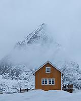 Yellow robu cabin and Olstind mountain peak emerging from clouds, Sakrisøy, Lofoten Islands, Norway