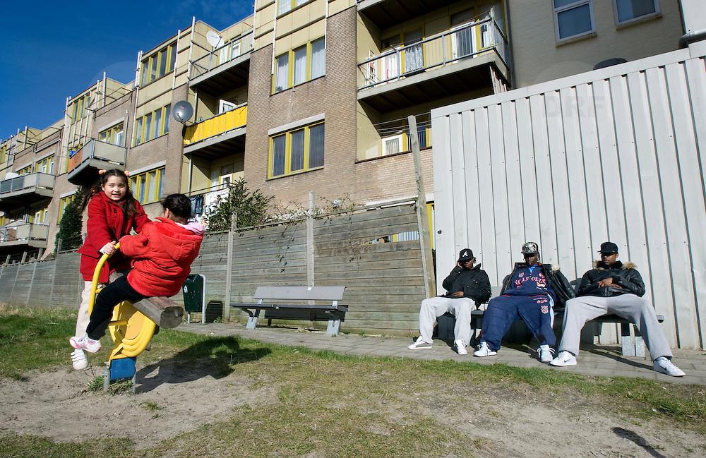 Nederland Rotterdam 14 maart 2008 20080314 .Stadsgezicht achterstandswijk Hillesluis Rotterdam Zuid, allochtone jongeren zitten op bankje in zonnetje en meisjes spelen bij braakliggend terrein dat tijdelijk als speelplaats is ingericht tot bestemming van de locatie duidelijk is. ..Foto David Rozing