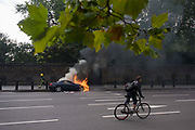 A cyclist pedals past a Mercedes as it burns at the side of the road at Hyde Park Corner in central London. Traffic has been diverted around this otherwise busy road junction and the car continues to burn as the fire brigade arrives to assess the dangers. A firefighter walks back towards an unseen fire engine before returning to deal with the serious fire to the engine and then extinguishes the flames. But the cyclist pedals around the vehicles and makes his escape on a traffic-free road towards Victoria. The wall in the background surrounds the grounds of Buckingham Palace.