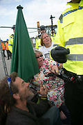 12 local activists locked themselves in specially made arm tubes to block the entrance to Quadrillas drill site in New Preston Road, July 03 2017, Lancashire, United Kingdom. Michelle Martin and her protector are asaked to leave in spite of she is locked on. The 13 activists included 3 councillors; Julie Brickles, Miranda Cox and Gina Dowding and Nick Danby, Martin Porter, Jeanette Porter,  Michelle Martin, Louise Robinson,<br /> Alana McCullough, Nick Sheldrick, Cath Robinson, Barbara Cookson, Dan Huxley-Blyth. The blockade is a repsonse to the emmidiate drilling for shale gas, fracking, by the fracking company Quadrilla. Lancashire voted against permitting fracking but was over ruled by the conservative central Government. All the activists have been active in the struggle against fracking for years but this is their first direct action of peacefull protesting. Fracking is a highly contested way of extracting gas, it is risky to extract and damaging to the environment and is banned in parts of Europe . Lancashire has in the past experienced earth quakes blamed on fracking.
