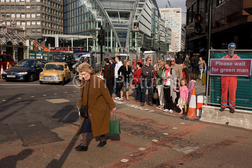 An elderly lady jaywalker crosses a road junction on a red pedestrian light in central London during temporary street improvements. With other road-users staying safely on the pavement after the lights have changed in waiting traffic's favour, the old woman blatantly or innocently makes her way across the crossing risking being run over by dangerous drivers. Behind her is a hum effigy of a workman contractor that holds a sign discouraging pedestrians from crossing on red lights.