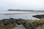 People on Summer holiday enjoy paddleboarding on the sea on 17th August 2021 in Pembrokeshire, Wales, United Kingdom. Newport is a town, parish, community, electoral ward and ancient port of Parrog, on the Pembrokeshire coast in West Wales at the mouth of the River Nevern in the Pembrokeshire Coast National Park.