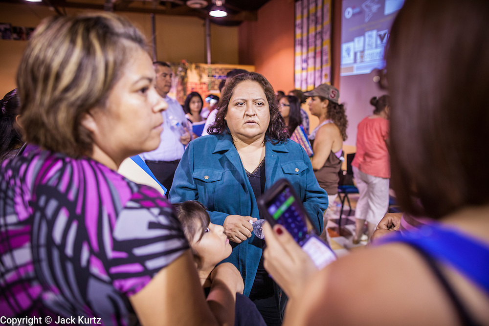 """18 AUGUST 2012 - PHOENIX, AZ:  EMILIA BANUELOS, an immigration lawyer, talks to young people about the """"deferred action"""" program during a deferred action workshop in Phoenix. More than 1000 people attended a series of 90 minute workshops in Phoenix Saturday on the """"deferred action"""" announced by President Obama in June. Under the plan, young people brought to the US without papers, would under certain circumstances, not be subject to deportation. The plan mirrors some aspects the DREAM Act (acronym for Development, Relief, and Education for Alien Minors), that immigration advocates have sought for years. The workshops were sponsored by No DREAM Deferred Coalition.  PHOTO BY JACK KURTZ"""