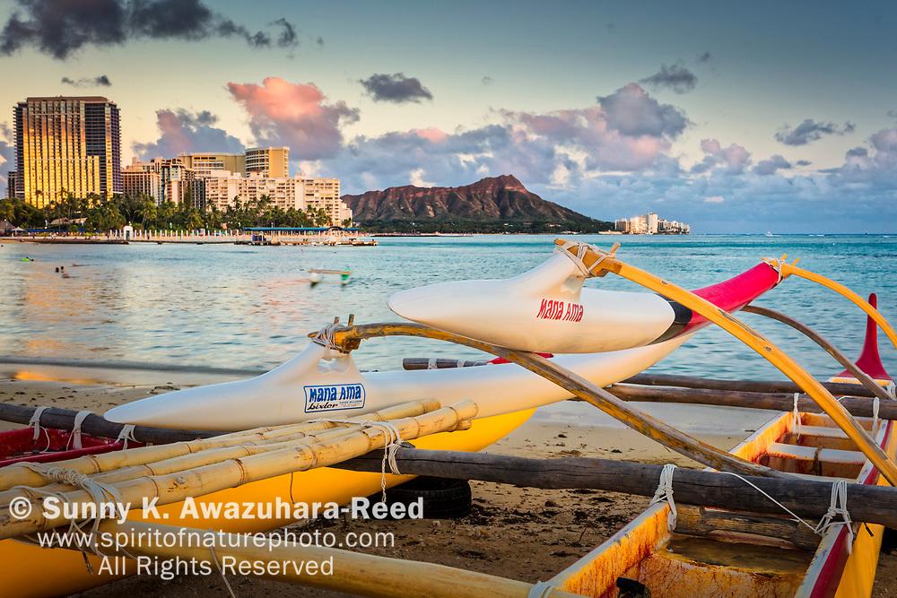 Outrigger canoe on Kahanamoku Beach.  Diamond Head and Highrise hotels glow  at sunset. Honolulu, Oahu, Hawaii.