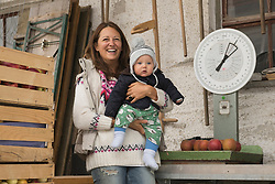 Organic farmer woman with her baby son standing in farm and scale in the background, Bavaria, Germany