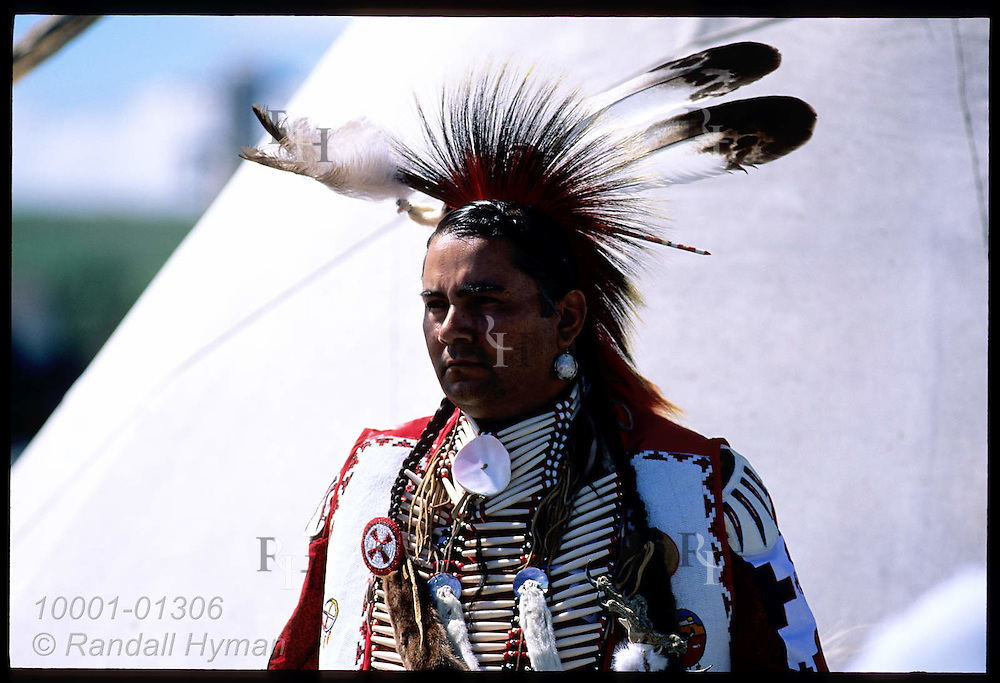 Costumed man from Fort Belknap Indian Reservation stands near teepee during Lewis & Clark Festival; Great Falls, Montana
