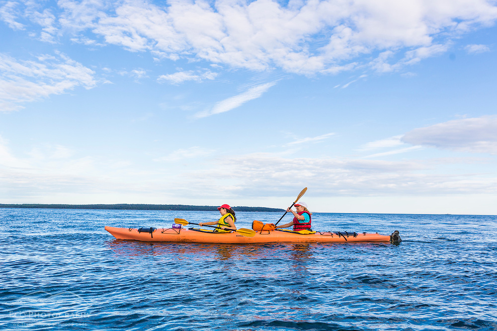 A woman and her daughter sea kayaking in Frenchman Bay, Acadia National Park, Maine. Porcupine Islands.