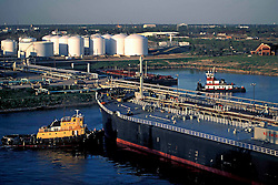 A tug boat pushing an oil tanker.