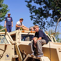 072614       Cable Hoover<br /> <br /> Samuel Van Osdell, right, Jacob Lewis and Sidney Van Osdell climb on top of the Ramah Navajo Police's armored transport vehicle after the Pioneer Days parade in Ramah Saturday.