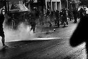 """Athens, Greece - Clashes between police and protesters near tear gas. Greek economical crisis started in 2008. The so-called Austerity measures imposed to the country by the """"Troika"""" (European Union, European Central Bank, and International Monetary Fund) to reduce its debt, were followed by a deep recession and the worsening of life conditions for millions of people. Unemployment rate grew from 8.5% in 2008 to 25% in 2012 (source: Hellenic Statistical Authority). <br /> Bruno Simões Castanheira"""