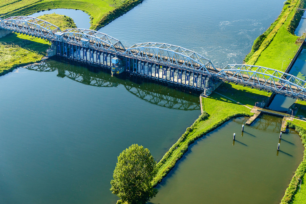 Nederland, Noord-Brabant, Grave, 23-08-2016; stuw in de rivier de Maas, dient om de waterloop te reguleren en het peil te beheren. Naast de stuw de schutsluis voor de scheepvaart en de  vistrap waardoor de vissen langs de stuw stroomopwaarts kunnen zwemmen. De vakwerkbrug is voor de lokaal verkeer over de rivier.<br /> Flood barrier in the river Meuse to regulate the watercours and manage the water level<br /> Next to the barrier the lock for barges and the newly built 'fish stairway' (which alows fish to pass the barrier). The lattice bridge is for the local road over the river<br /> aerial photo (additional fee required); <br /> luchtfoto (toeslag op standard tarieven);<br /> copyright foto/photo Siebe Swart