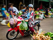 08 JUNE 2017 - BANGKOK, THAILAND: A shopper on a motorcyle in Khlong Toey Market, Bangkok's main fresh market. Thai consumer confidence dropped for the first time in six months in May following a pair of bombings in Bangkok, low commodity prices paid to farmers and a sharp rise in the value of the Thai Baht versus the US Dollar and the EU Euro. The Baht is surging because of political uncertainty, related to Donald Trump, in the US and Europe. The Baht's rise is being blamed for a drop in Thai exports. This week the Baht has been trading at around 33.90 Baht to $1US, it's highest point in two years.      PHOTO BY JACK KURTZ